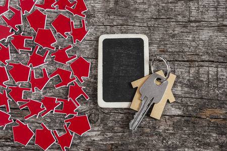 realestate: Symbol of the house with silver key on vintage wooden background
