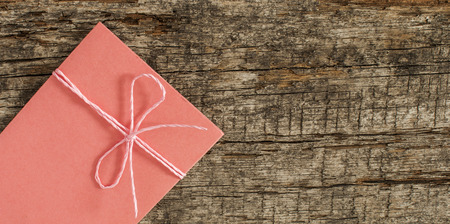 old envelope: Red envelope wrapped with jute twine on a wooden background Stock Photo