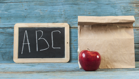 Paper lunch bag and small blackboard on wooden background
