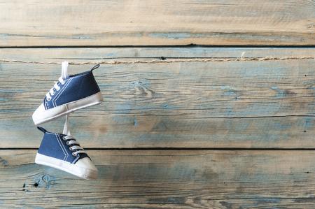 Sapatos de bebê pendurado no varal colorido sobre fundo de madeira Foto de archivo - 94402572