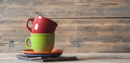 Colorful coffee cups against rustic wooden wall with copy space