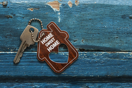 House key on a house shaped keychain resting on wooden background, concept for real estate