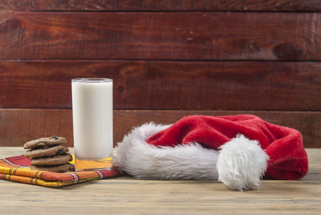 Christmas cookies and a glass of milk for Santa on wooden table. New year's concept. Copy space