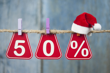 Sale tags with sign percent hanging from brown rope over wooden wall. Happy New Year sale concept