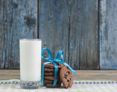 Glass of milk and chocolate chip cookies on wooden background