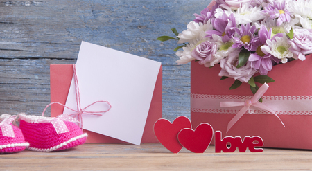 Small child shoes and beautiful flower bouquet on the wooden table background