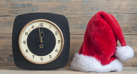 Santa Claus hat on New Year's night on the old clock showing twelve o'clock on the wooden background Archivio Fotografico