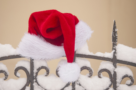 Santa Claus hat on old fashioned spike fence against yellow wall, some snow. Christmas celebrate concept