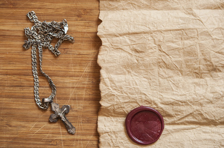 Closeup of silver Christian cross on a old paper over aged wood background