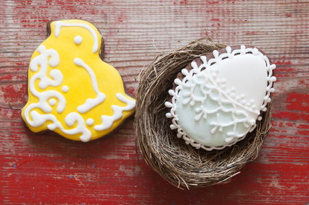 Colorful easter cookies in nest on wooden background