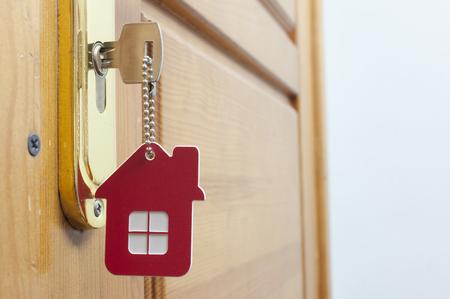 Een sleutel in een slot met een huisje erop Stockfoto