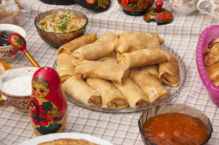 Stapel Russische pannenkoeken blini en traditionele houten poppen matrioshka. Stockfoto