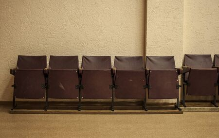 Old, brown, wooden cinema chairs put in a row.