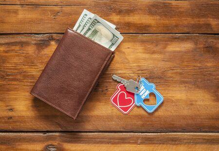 Schlüsselhaus und Ledergeldbörse auf altem Holztisch.
