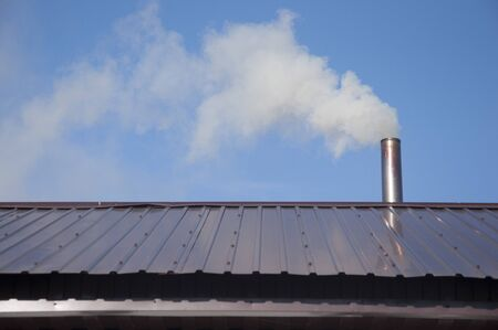 Chimney made of iron. Smoke from the chimney, heating. smoke billowing. coming out of a house chimney against a blue sky background