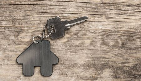 Symbol of the house with silver key on vintage wooden background. Real estate concept
