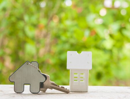 House key on a house shaped keychain on natural background. Real estate concept