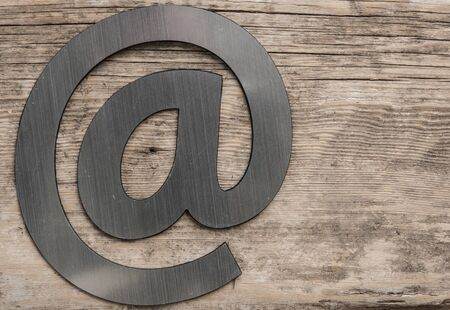 silver email symbol on wood texture