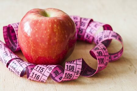 Red apple and measuring tape on wooden table. Concept of proper diet and healthy lifestyle. Reklamní fotografie