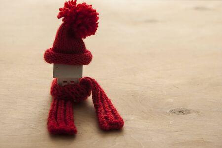Modello di casa con berretto lavorato a maglia e sciarpa sul tavolo su sfondo bianco. Concetto di riscaldamento