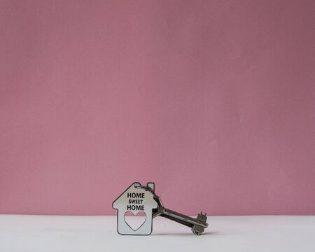 Key and house shape with text home sweet home on white background.