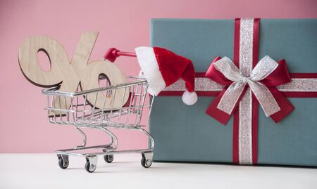 discount signs with Santa hat and christmas gift box over pink background. Christmas sale Stock Photo