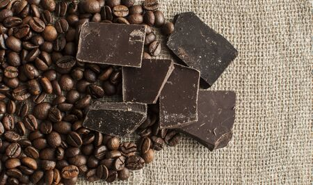 Pile of coffee beans with chocolate on burlap cloth background