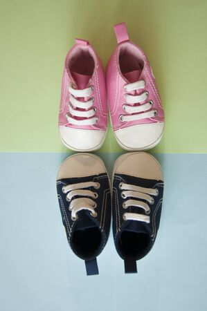 colorful canvas shoes or sneakers for kids or baby foot on paper background view with copy space.