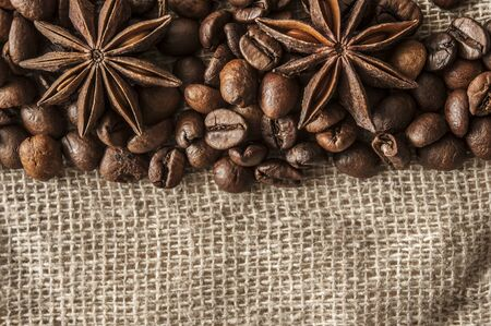 Roasted coffee beans and spice badian on a background of burlap. Coffee beans pile from top with copy space for text.