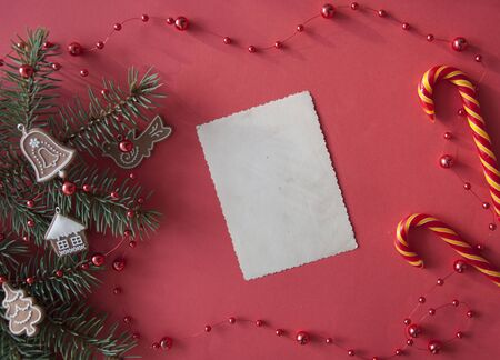 Christmas composition. Fir tree branches and decorations on red lay, top view, copy space