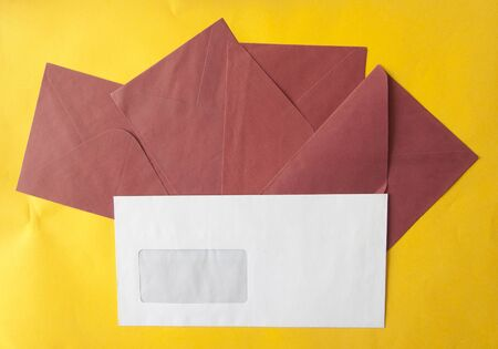 envelopes on yellow table top view. Mockup for business mail, blogging and office correspondence. Flat lay.
