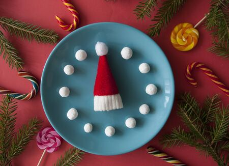 Christmas background with candy canes and blue plate on red paper background. Top view
