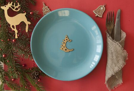 Christmas table setting from above. Elegant empty light blue plate, cutlery and fir branch on red paper background. Top view