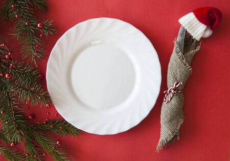 Christmas table setting from above. Elegant empty light white plate, cutlery and fir branch on red paper background. Top view