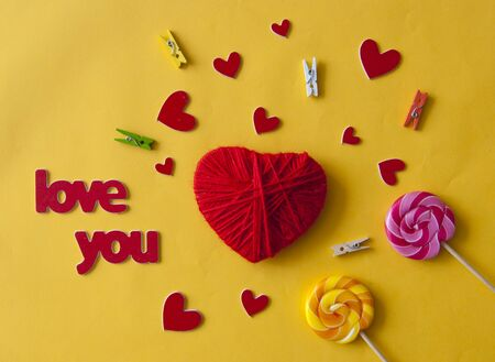 Love word, heart and lollipop candies on yellow paper  background. Valentines day, mothers day, holiday. Top view. Standard-Bild - 133982704