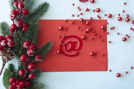 Christmas decorations, fir branches, red envelope, red berries on pastel blue background. Christmas, New Year, winter concept. Flat lay, top view, copy space