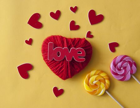 Love word, heart and lollipop candies on yellow paper  background. Valentines day, mothers day, holiday. Top view. Standard-Bild - 133982711