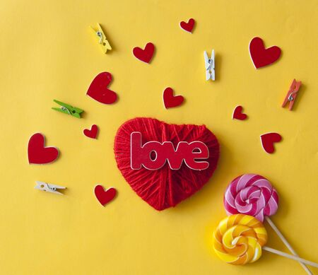 Love word, heart and lollipop candies on yellow paper  background. Valentines day, mothers day, holiday. Top view. Standard-Bild - 133982727