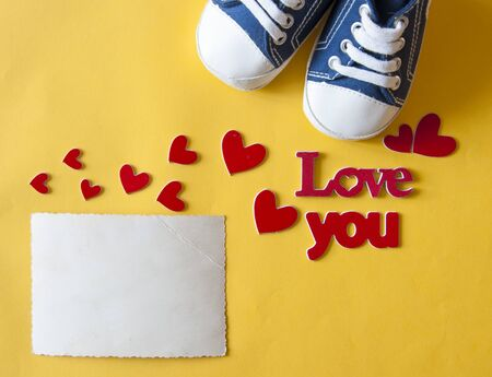 Festive background decoration for birthday celebration with red love lettering, heart shaped and colorful kid sneakers for a baby shower. Top view. Banque d'images