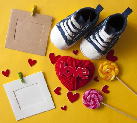 Festive background decoration for birthday celebration with red love lettering, heart shaped and colorful kid sneakers for a baby shower. Top view. Stockfoto