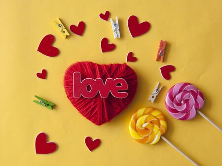 Love word, heart and lollipop candies on yellow paper  background. Valentines day, mothers day, holiday. Top view. Standard-Bild - 133982742