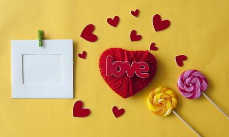 Love word, heart and lollipop candies on yellow paper  background. Valentines day, mothers day, holiday. Top view.