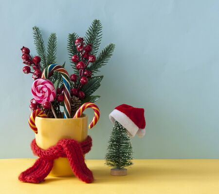 Christmas or new year card. Christmas candy canes in yellow mug with berries holly branches and Christmas decoration.