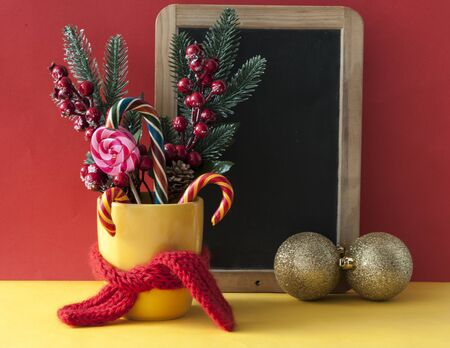 Christmas or new year card. Christmas candy canes in yellow mug with berries holly branches and Christmas decoration. Banco de Imagens
