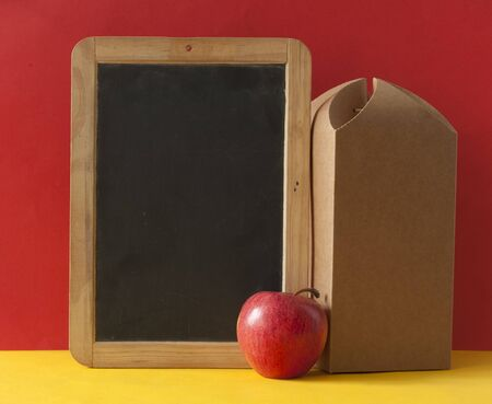 School lunch. Brown paper bag and a red apple on colorful paper background Zdjęcie Seryjne