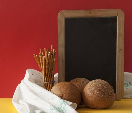 Homemade round buns with blank chalkboard and salted straw snack on colorful paper background Zdjęcie Seryjne