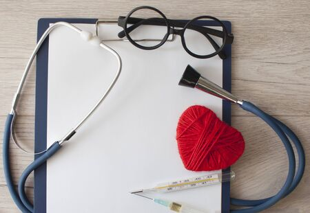 Doctors Day , the cardiologist's day, blue stethoscope with a red heart and blank your clipboard on a background of white boards, diagnosis of heart disease Stok Fotoğraf