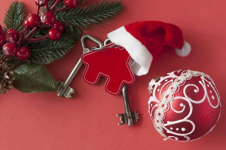 Christmas decorations: decorative house with key to the lock and Santa hat on red paper background, concept of finance and housing loans  Zdjęcie Seryjne