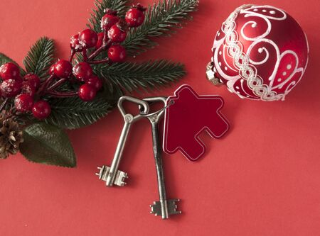 Christmas decorations: decorative house and key to the lock on red paper background, concept of finance and housing loans