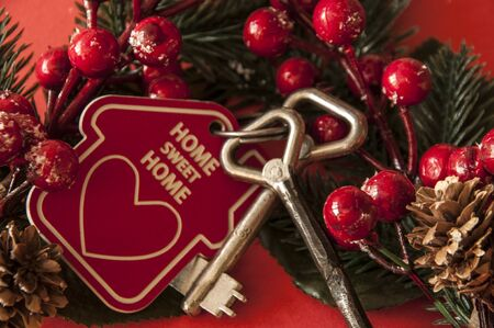Beautiful Christmas background: decorative house and key to the lock on red background, flat lay. Space for text. Concept of finance and housing loans. Top view